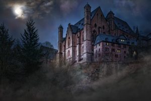Creepy mansion on a hill at night